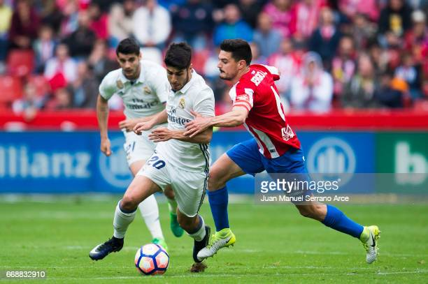 Marco Asensio of Real Madrid duels for the ball with Sergio Alvarez of Real Sporting de Gijon during the La Liga match between Real Sporting de Gijon...