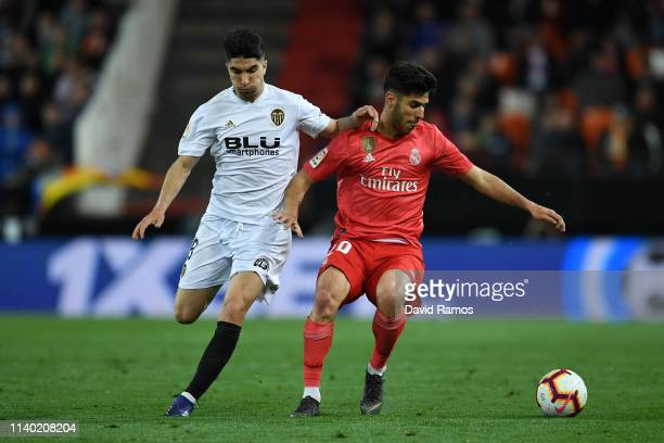 Marco Asensio of Real Madrid holds off Carlos Soler of Valencia during the La Liga match between Valencia CF and Real Madrid CF at Estadio Mestalla...
