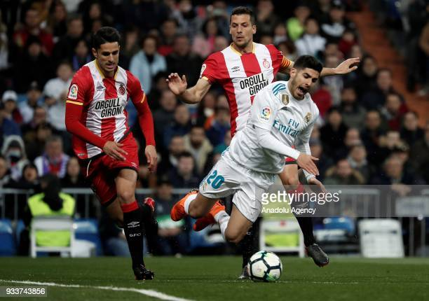 Marco Asensio of Real Madrid in action against Juanpe and Alex Granell of Girona during the La Liga soccer match between Real Madrid and Girona at...