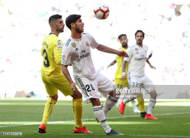 Marco Asensio of Real Madrid is challenged by Alvaro Gonzalez of Villereal during the La Liga match between Real Madrid CF and Villarreal CF at...