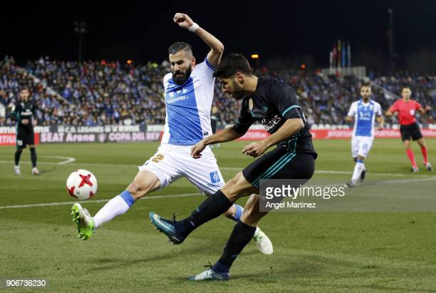 Marco Asensio of Real Madrid is challenged by Dimitrios Siovas of Leganes during the Spanish Copa del Rey Quarter Final First Leg match between...