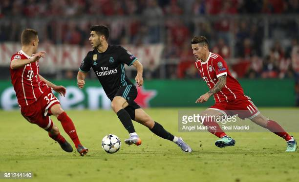 Marco Asensio of Real Madrid is challenged by James Rodriguez and Joshua Kimmich of Bayern Muenchen during the UEFA Champions League Semi Final First...