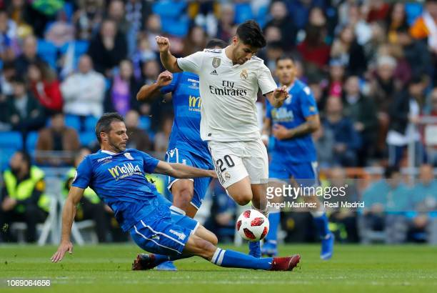 Marco Asensio of Real Madrid is challenged by Richi Segura of Melilla during the Copa del Rey fourth round second leg match between Real Madrid and...