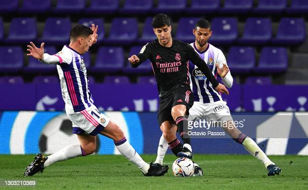 Marco Asensio of Real Madrid is challenged by Ruben Alcaraz and Joaquin Fernandez of Real Valladolid during the La Liga Santander match between Real...