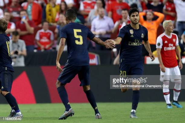 Marco Asensio of Real Madrid is congratulated by his teammate Raphael Varane after scoring a goal against Arsenal during their 2019 International...