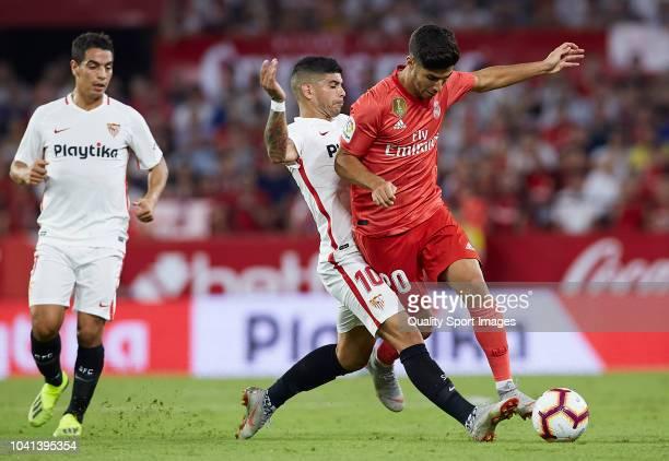 Marco Asensio of Real Madrid is tackled by Ever Banega of Sevilla during the La Liga match between Sevilla FC and Real Madrid CF at Estadio Ramon...