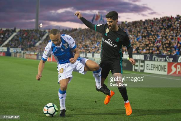 Marco Asensio of Real Madrid is tackled by Nabil El Zhar of CD Leganes during the La Liga match between Leganes and Real Madrid at Estadio Municipal...