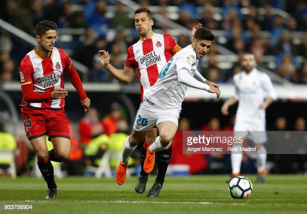 Marco Asensio of Real Madrid is tackled by with Alex Granell of Girona during the La Liga match between Real Madrid and Girona at Estadio Santiago...