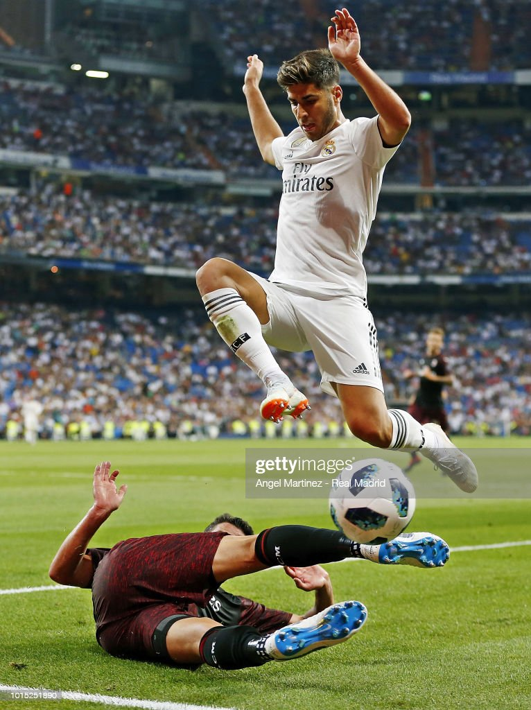 Marco Asensio of Real Madrid jumps over Mateo Musacchio of AC Milan during the Trofeo Santiago Bernabeu match between Real Madrid and AC Milan at Estadio Santiago Bernabeu on August 11, 2018 in Madrid, Spain.