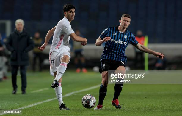 Marco Asensio of Real Madrid makes a pass whilst under pressure from Robin Gosens of Atalanta B.C. During the UEFA Champions League Round of 16 match...