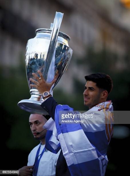Marco Asensio of Real Madrid raises The UEFA Champions League trophy during celebrations at Cibeles Fountain after winning the 2016/17 UEFA Champions...