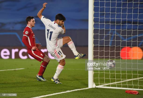 Marco Asensio of Real Madrid scores their team's second goal while pressured by Andrew Robertson of Liverpool during the UEFA Champions League...