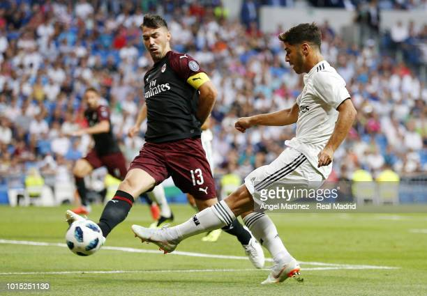 Marco Asensio of Real Madrid shoots on goal past Alessio Romagnoli of AC Milan during the Trofeo Santiago Bernabeu match between Real Madrid and AC...