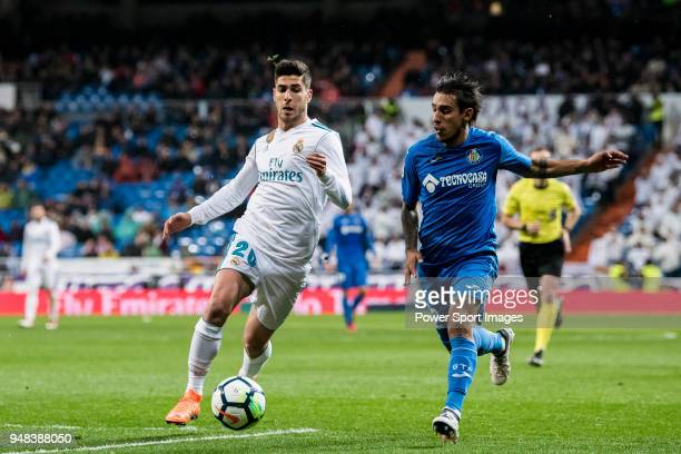 Marco Asensio Willemsen of Real Madrid fights for the ball with Damian Nicolas Suarez Suarez of Getafe CF during the La Liga match between Real...
