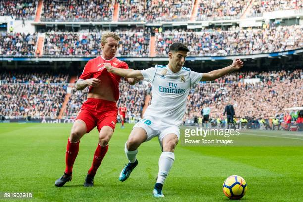 Marco Asensio Willemsen of Real Madrid fights for the ball with Simon Kjaer of Sevilla FC during the La Liga 201718 match between Real Madrid and...