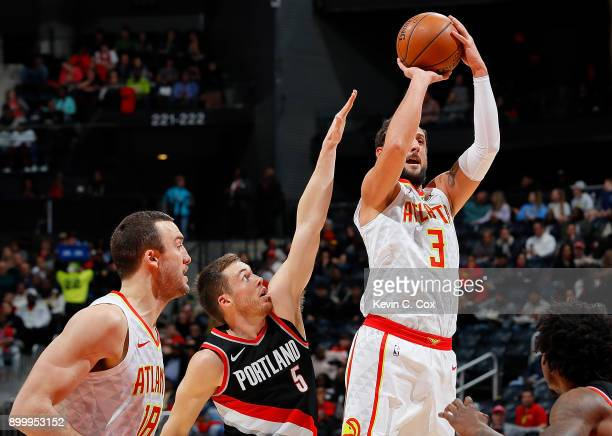 Marco Belinelli of the Atlanta Hawks attempts a shot against Pat Connaughton and Ed Davis of the Portland Trail Blazers at Philips Arena on December...