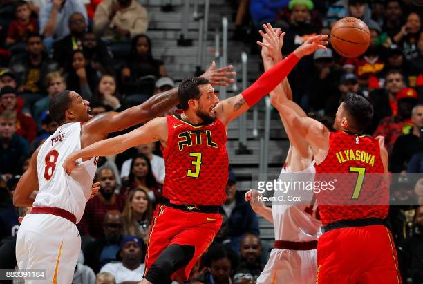 Marco Belinelli of the Atlanta Hawks knocks away a rebound against Channing Frye and Cedi Osman of the Cleveland Cavaliers at Philips Arena on...