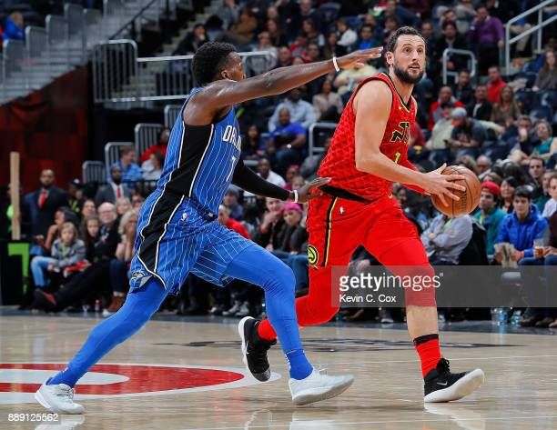 Marco Belinelli of the Atlanta Hawks looks to shoot against Shelvin Mack of the Orlando Magic at Philips Arena on December 9 2017 in Atlanta Georgia...