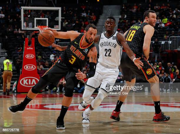 Marco Belinelli of the Atlanta Hawks runs around a screen by Miles Plumlee against Caris LeVert of the Brooklyn Nets at Philips Arena on December 4...