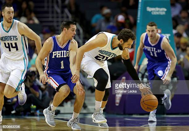 Marco Belinelli of the Charlotte Hornets and TJ McConnell of the Philadelphia 76ers go after a loose ball during their game at Spectrum Center on...