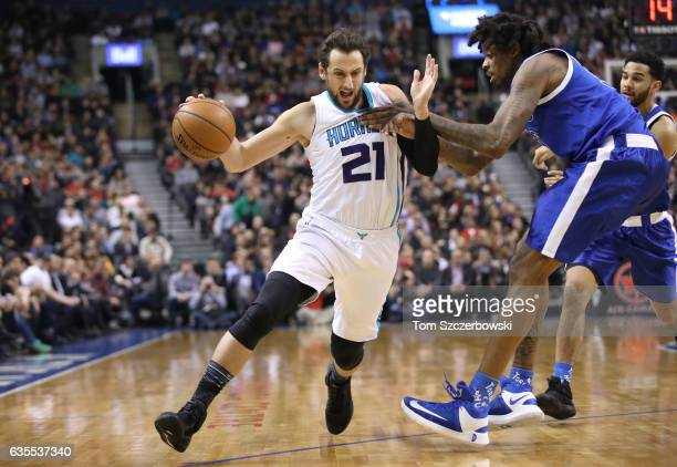 Marco Belinelli of the Charlotte Hornets goes to the basket as he is guarded by Lucas Nogueira of the Toronto Raptors during NBA game action at Air...