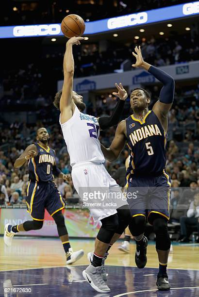 Marco Belinelli of the Charlotte Hornets looks to pass around Lavoy Allen of the Indiana Pacers during their game at Spectrum Center on November 7...