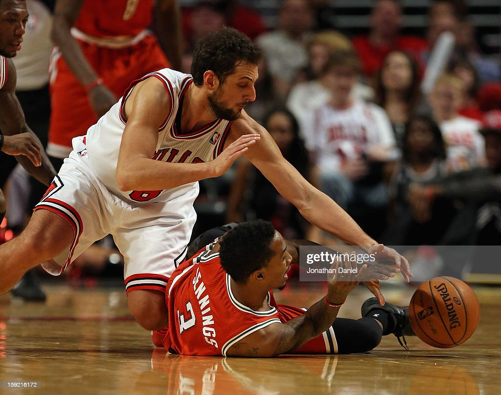 Marco Belinelli #8 of the Chicago Bulls and Brandon Jennings #3 of the Milwaukee Bucks battle for a loose ball at the United Center on January 9, 2013 in Chicago, Illinois. The Bucks defeated the Bulls 104-96.