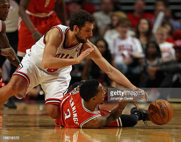 Marco Belinelli of the Chicago Bulls and Brandon Jennings of the Milwaukee Bucks battle for a loose ball at the United Center on January 9 2013 in...