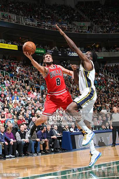 Marco Belinelli of the Chicago Bulls attempts a layup against DeMarre Carroll of the Utah Jazz at Energy Solutions Arena on February 08 2013 in Salt...