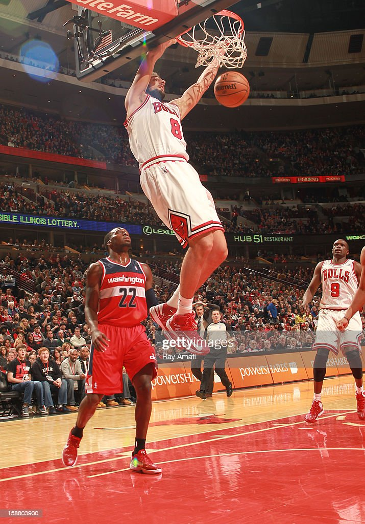 Marco Belinelli #8 of the Chicago Bulls dunks against Shelvin Mack #22 of the Washington Wizards on December 29, 2012 at the United Center in Chicago, Illinois.