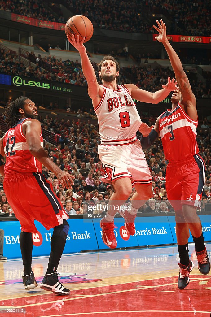 Marco Belinelli #8 of the Chicago Bulls goes to the basket against Nené #42 and Bradley Beal #3 of the Washington Wizards on December 29, 2012 at the United Center in Chicago, Illinois.