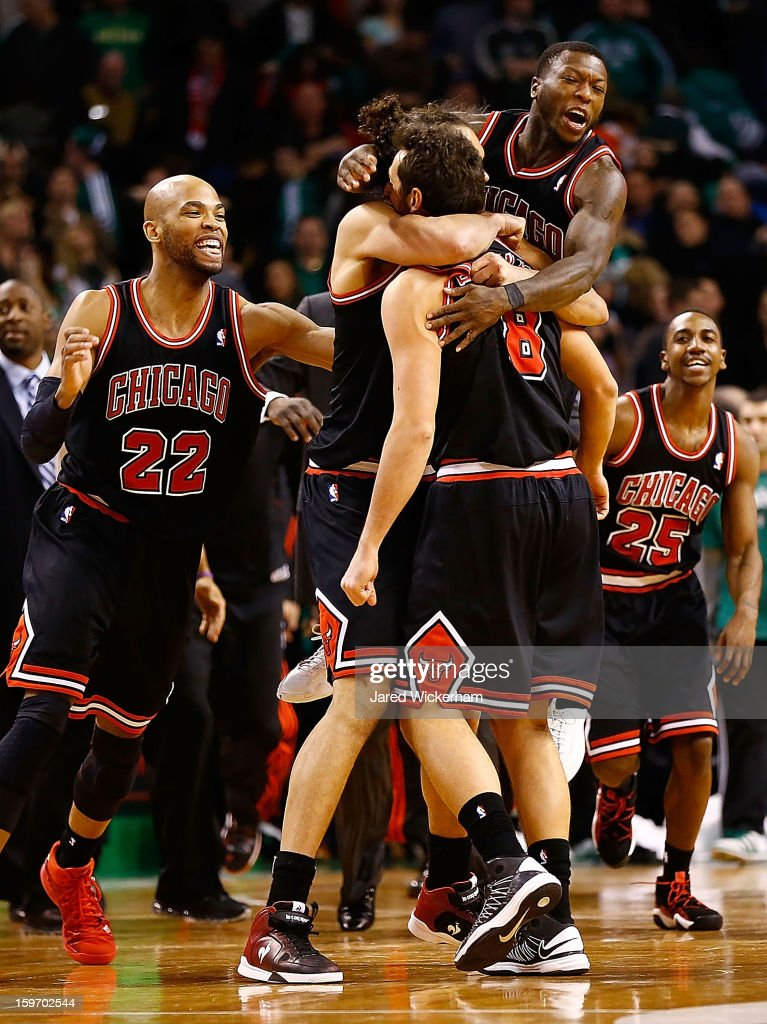 Marco Belinelli #8 of the Chicago Bulls is embraced by teammates Joakim Noah #13 and Nate Robinson #2 of the Chicago Bulls after scoring the game-winning shot with 3.1 seconds remaining in overtime against the Boston Celtics during the game on January 18, 2013 at TD Garden in Boston, Massachusetts.