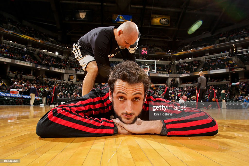 Marco Belinelli #8 of the Chicago Bulls stretches with a trainer before a game against the Indiana Pacers on March 3, 2013 at Bankers Life Fieldhouse in Indianapolis, Indiana.