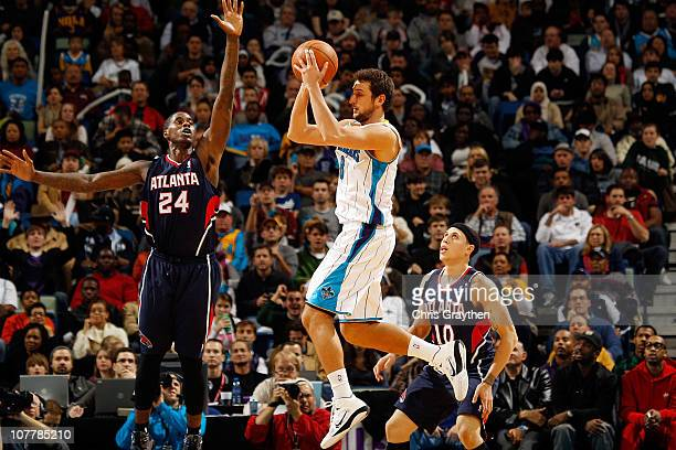 Marco Belinelli of the New Orleans Hornets passes the ball around Marvin Williams of the Atlanta Hawks at the New Orleans Arena on December 26 2010...