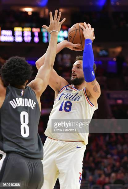 Marco Belinelli of the Philadelphia 76ers takes a jump shot over Spencer Dinwiddie of the Brooklyn Nets at the Wells Fargo Center on March 16 2018 in...