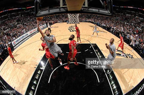 Marco Belinelli of the San Antonio Spurs drives to the basket against the Houston Rockets during the game at the ATT Center on December 25 2013 in...