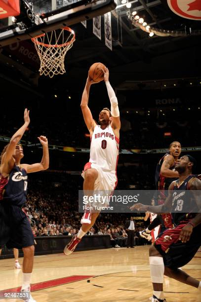 Marco Belinelli of the Toronto Raptors finishes the break with the slam dunk in front of LeBron James of the Cleveland Cavaliers during a game on...