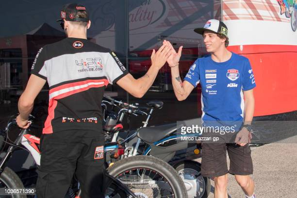 Marco Bezzecchi of Italy and Pruestel GP grets Stefano Manzi of Italy and Forward Racing Team in paddock during the MotoGP of Aragon Previews at...
