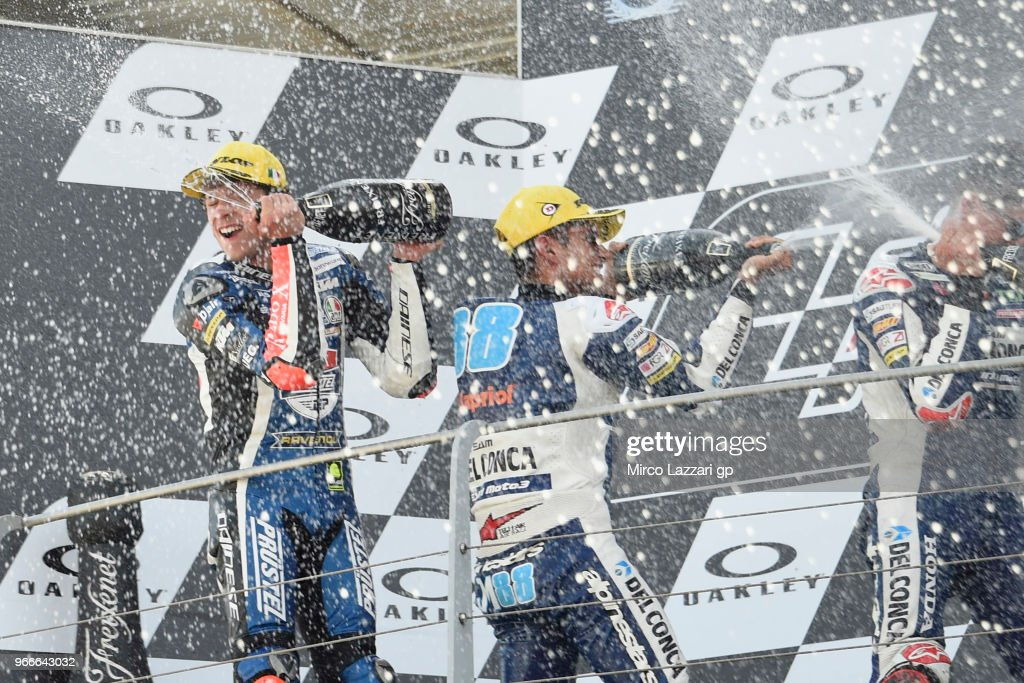 Marco Bezzecchi of Italy and Pruestel GP, Jorge Martin of Spain and Del Conca Gresini Moto3, and Fabio Di Giannantonio of Italy and Del Conca Gresini Moto3 celebrate with champagne on the podium at the end of the Moto3 race during the MotoGp of Italy - Race at Mugello Circuit on June 3, 2018 in Scarperia, Italy.