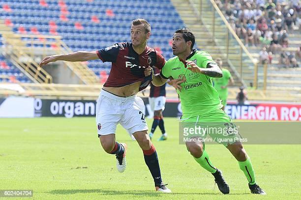 Marco Borriello of Cagliari Calcio competes the ball with Daniele Gastaldello of Bologna FC during the Serie a match between Bologna FC and Cagliari...