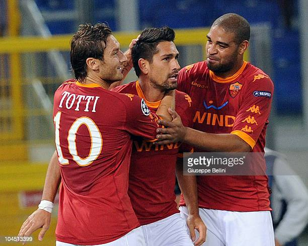 Marco Borriello of Roma is congratulated by teammates Francesco Totti and Adriano after scoring the goal 20 during the UEFA Champions League group E...