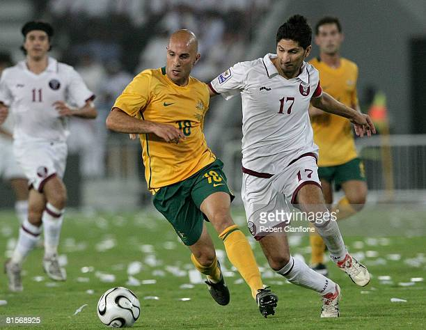 Marco Bresciano of Australia is challenged by Wesam Rizik of Qatar during the 2010 FIFA World Cup qualifying match between Qatar and Australia at...