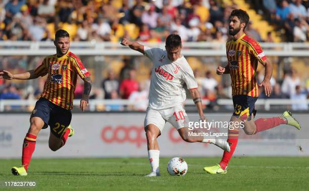 Marco Calderoni and Luca Rossettini of Lecce competes for the ball with Paulo Dybala of Juventus during the Serie A match between US Lecce and...