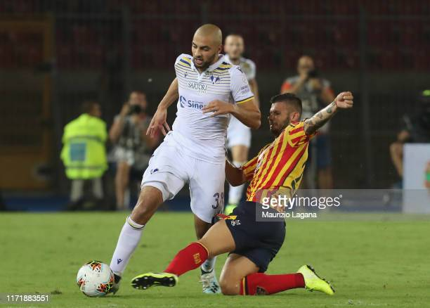 Marco Calderoni of Lecce competes for the ball with Sofyan Amrabat of Hellas Verona during the Serie A match between US Lecce and Hellas Verona at...
