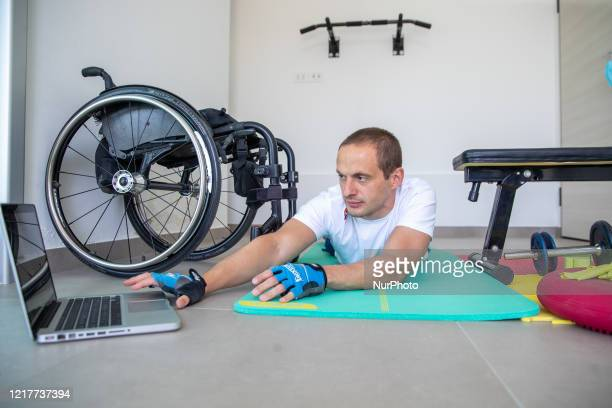 Marco Dolfin, an athlete of the Italian Paralympic swimming team, participates in a team training using an online conference call from the gym of his...
