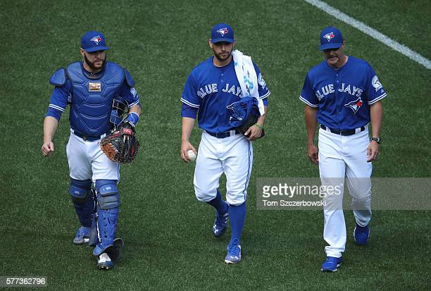 Marco Estrada of the Toronto Blue Jays and Russell Martin and pitching coach Pete Walker make their way from the bullpen to the dugout before the...