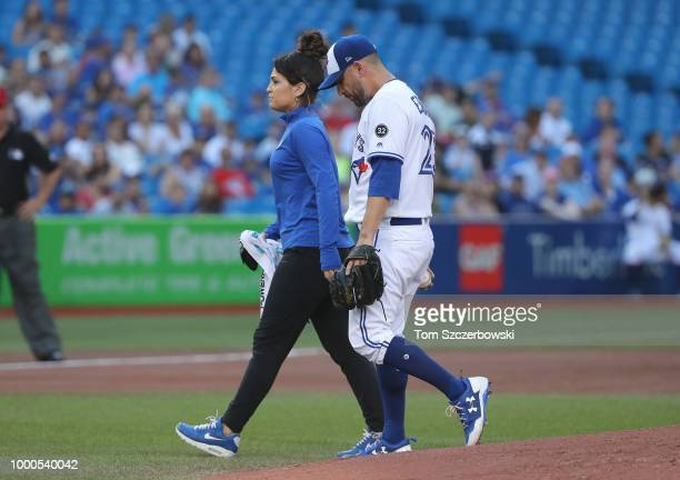 Marco Estrada of the Toronto Blue Jays exits the game with head athletic trainer Nikki Huffman in the first inning during MLB game action against the...