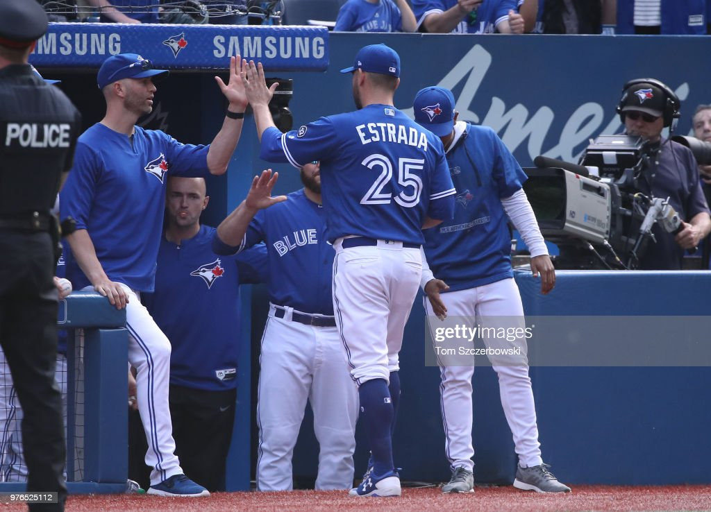 Marco Estrada #25 of the Toronto Blue Jays is congratulated by J.A. Happ #33 and teammates on the top step of the dugout as he comes out of the game in the seventh inning during MLB game action against the Washington Nationals at Rogers Centre on June 16, 2018 in Toronto, Canada.
