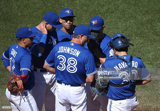 Marco Estrada of the Toronto Blue Jays is visited on the mound by bullpen coach Dane Johnson as Dioner Navarro looks on in the fifth inning during...