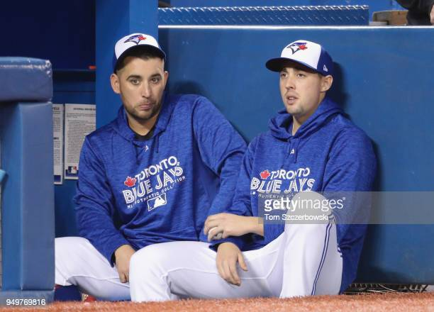 Marco Estrada of the Toronto Blue Jays talks to Aaron Sanchez on the top step of the dugout during MLB game action against the Kansas City Royals at...